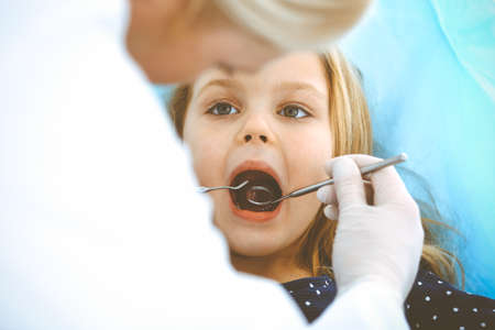 Little baby girl sitting at dental chair with open mouth during oral check up while doctor. Visiting dentist office. Medicine concept. Toned photo Archivio Fotografico - 137436533