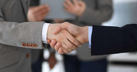 Uomini d'affari che si stringono la mano mentre sono in piedi con i colleghi dopo un incontro o una negoziazione, primo piano. Gruppo di uomini d'affari e donne sconosciuti in un ufficio moderno. Concetto di lavoro di squadra, partnership e stretta di mano, immagine tonica. Archivio Fotografico