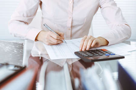 Bookkeeper woman or financial inspector making report, calculating or checking balance, close-up. Business, audit or tax concepts.