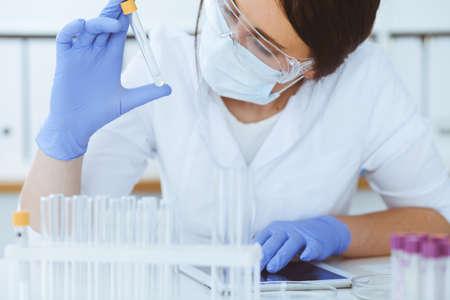 Primer plano de mujer científico profesional en gafas protectoras haciendo experimento con reactivos o análisis de sangre en laboratorio. Medicina, biotecnología y concepto de investigación.