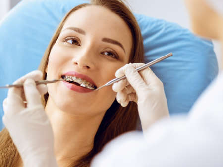 Smiling young woman with orthodontic brackets examined by dentist at dental clinic. Healthy teeth and medicine concept