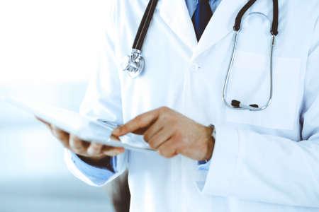 Hombre médico con tableta para investigación en red o tratamiento virtual de enfermedades, primer plano de las manos. Perfecto servicio médico en clínica. Medicina moderna, datos médicos y conceptos sanitarios. Imagen tonificada. Foto de archivo
