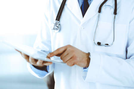 Uomo medico che utilizza computer tablet per la ricerca di rete o il trattamento delle malattie virtuali, primo piano delle mani. Servizio medico perfetto in clinica. Medicina moderna, dati medici e concetti sanitari. Immagine tonica. Archivio Fotografico