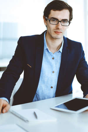 Businessman working with tablet computer in modern office. Headshot of male entrepreneur or company manager at workplace. Business concept