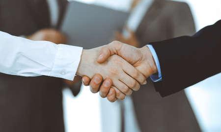 Uomini d'affari che si stringono la mano mentre sono in piedi con i colleghi dopo un incontro o una negoziazione, primo piano. Gruppo di uomini d'affari e donne sconosciuti in un ufficio moderno. Concetto di lavoro di squadra, partnership e stretta di mano, immagine tonica.
