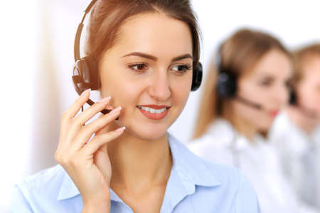 Call center. Focus on beautiful business woman using headset in sunny office