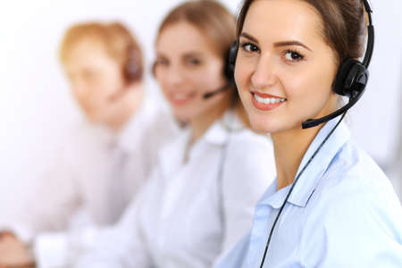 Call center. Focus on beautiful business woman using headset in sunny office.