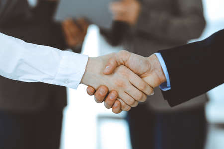 Business people shaking hands while standing with colleagues after meeting or negotiation, close-up. Group of unknown businessmen and women in modern office. Teamwork, partnership and handshake concept, toned picture. Banque d'images