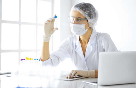 Professional female scientist in protective eyeglasses researching tube with reagents in laboratory. Concepts of medicine and research