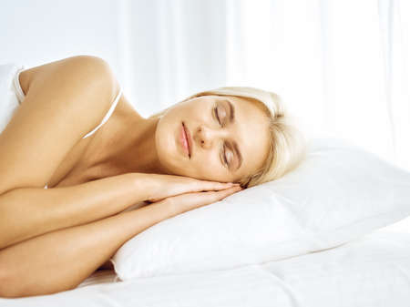 Beautiful young woman sleeping while lying in bed comfortably and blissfully. Good morning concept Stok Fotoğraf