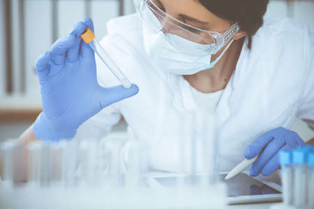 Close-up of professional female scientist in protective eyeglasses making experiment with reagents or blood test in laboratory. Medicine, biotechnology and research concept.