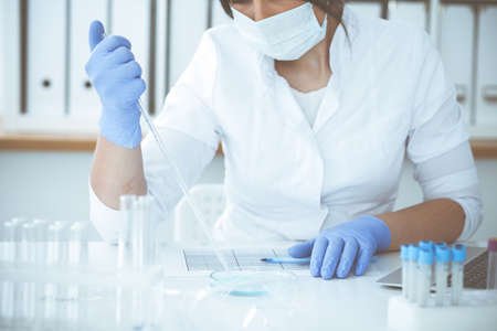 Close-up of professional female scientist in protective eyeglasses making experiment with reagents or blood test in laboratory. Medicine, biotechnology and research concept. Stock Photo
