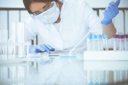 Gros plan sur une scientifique professionnelle portant des lunettes de protection faisant des expériences avec des réactifs ou un test sanguin en laboratoire. Concept de médecine, de biotechnologie et de recherche.