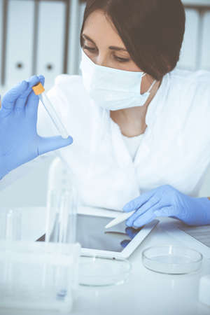Close-up of professional female scientist in protective eyeglasses making experiment with reagents or blood test in laboratory. Medicine, biotechnology and research concept. Foto de archivo