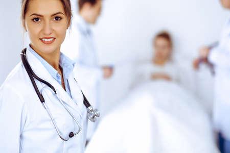 Doctora sonriendo en el fondo con el paciente en la cama y dos médicos Foto de archivo
