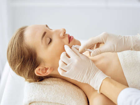 Beautiful woman receiving beauty injections with closed eyes. Beautician doctor hands doing beauty procedure to female face with syringe. Cosmetic medicine and surgery concept. Reklamní fotografie