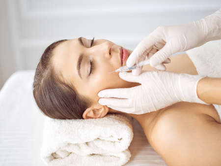 Beautician doing beauty procedure with syringe to face of young brunette woman. Cosmetic medicine and surgery, beauty injections. Zdjęcie Seryjne