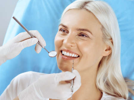 Smiling blonde woman examined by dentist at dental clinic. Healthy teeth and medicine concept