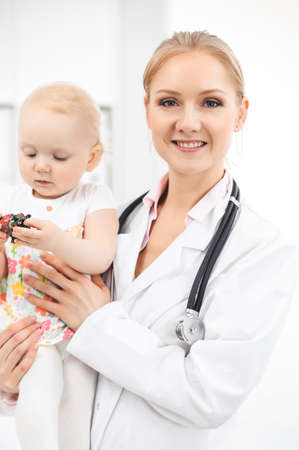 Doctor and patient toddler in hospital. Little girl dressed in dress with pink flowers is being examined by doctor with stethoscope. Medicine and health care concept