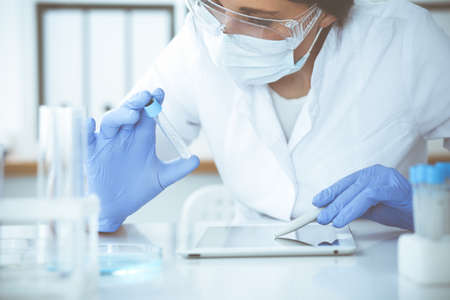 Close-up of professional female scientist in protective eyeglasses making experiment with reagents in laboratory. Medicine and research concept