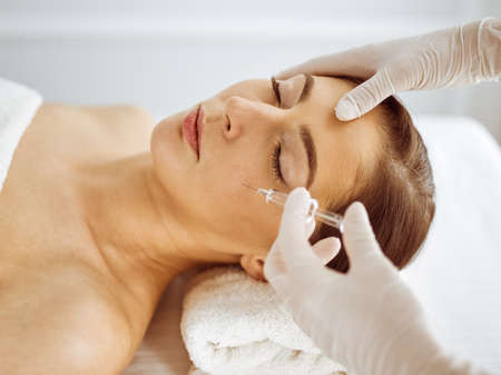 Beautician doing beauty procedure with syringe to face of young brunette woman. Cosmetic medicine and surgery, beauty injections.
