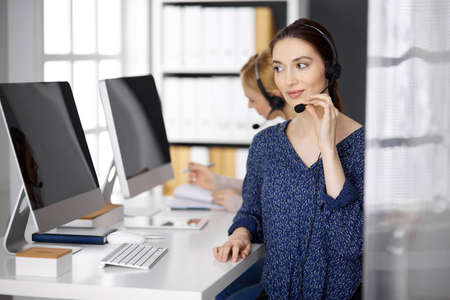 Latin american businesswoman talking by headset while sitting in office. Call center and diverse people group in business