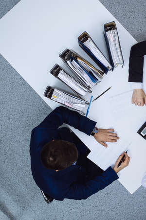 Business people at meeting, view from above. Bookkeeper or financial inspector making report, calculating or checking balance. Internal Revenue Service checking financial document. Audit and tax concept.