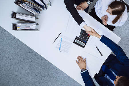 Business people shaking hands at meeting, view from above. Bookkeeper or financial inspector making report, calculating or checking balance. Internal Revenue Service checking financial document. Audit and tax concept