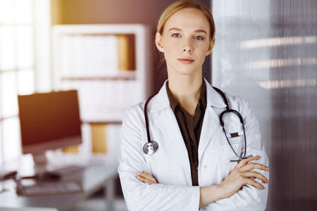 Cheerful smiling female doctor standing with arms crossed in clinic. Portrait of friendly physician woman. Medicine concept