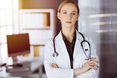 Doctora sonriente alegre de pie con los brazos cruzados en la clínica. Retrato de mujer amigable médico. Concepto de medicina