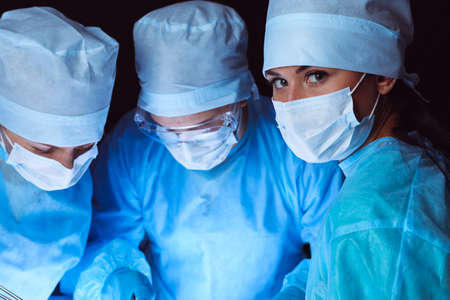 Group of surgeons wearing safety masks performing operation. Medicine concept. Stockfoto