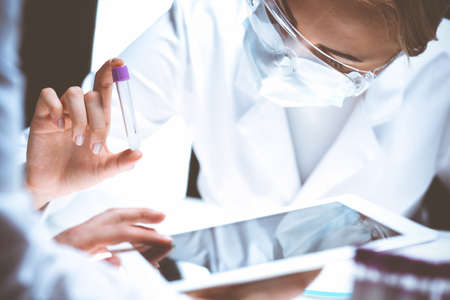 Coronavirus pandemic. Professional female scientist in protective eyeglasses researching tube with reagents in laboratory. Concepts of medicine and virus protection Stock Photo