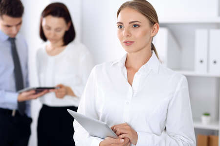 Beautiful blonde businesswoman standing straight in a brightly lit office at the background of colleagues or partners. Business headshot concept 写真素材