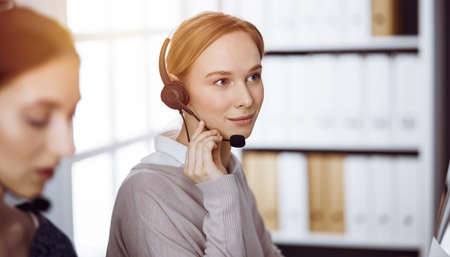 Businesswoman talking by headset in sunny office. Call center and diverse people group in business
