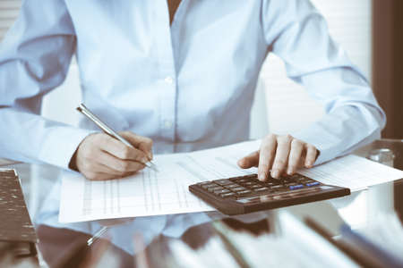 Bookkeeper woman or financial inspector making report, calculating or checking balance, close-up. Business, audit or tax concepts