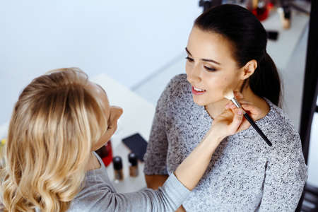 Professional makeup artist working with beautiful young woman. Bridal, fashion or style Banque d'images