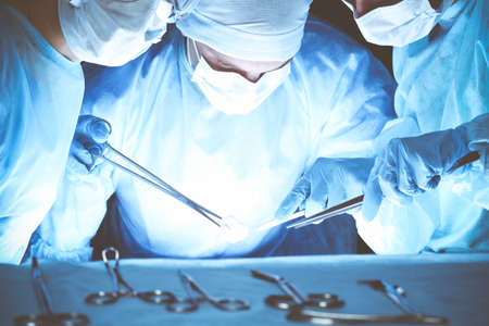 Group of surgeons wearing safety masks performing operation. Medicine concept