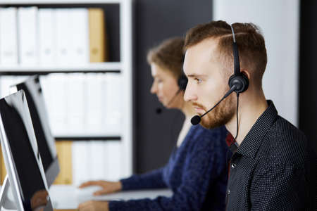 Red-bearded businessman talking by headset near his female colleague while sitting in modern office. Diverse people group in call center. Telemarketing and customer service