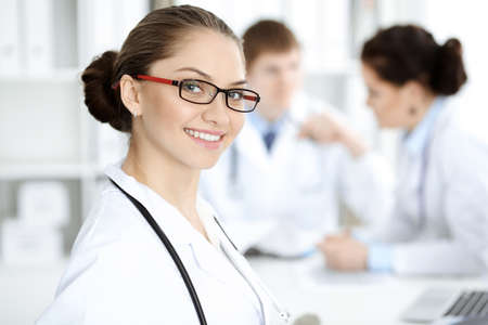 Happy smiling woman-doctor sitting and looking at camera at meeting with medical staff . Medicine concept Banque d'images