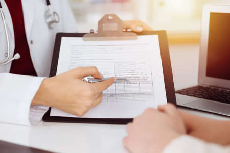 Unknown woman-doctor consulting patient and using clipboard with a medication history record in sunny room. Medicine concept Stockfoto