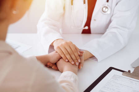 Hands of unknown woman-doctor reassuring her female patient in sunny room, close-up Reklamní fotografie