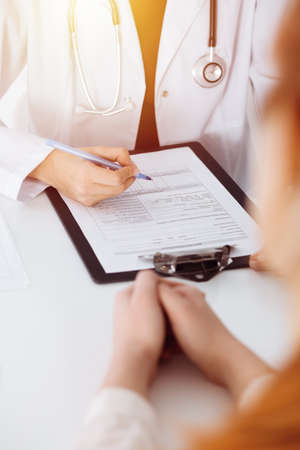 Unknown woman-doctor filling up an application form while consulting patient. in sunny room Medicine concept