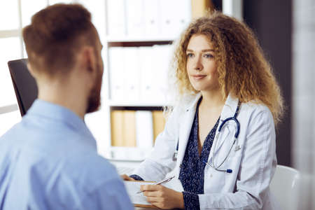 Female doctor and male patient discussing current health examination while sitting in sunny clinic. Medicine concept