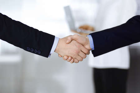 Business people shaking hands at meeting or negotiation, close-up. Group of unknown businessmen and a woman with a laptop stand together in a modern office. Teamwork, partnership and handshake concept. Standard-Bild