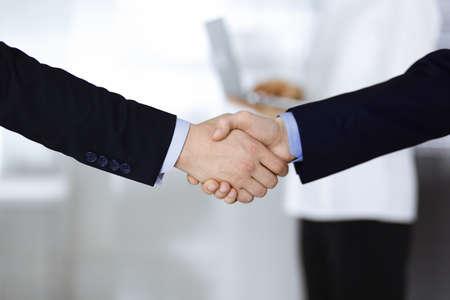 Gens d'affaires se serrant la main lors d'une réunion ou d'une négociation, gros plan. Un groupe d'hommes d'affaires inconnus et une femme avec un ordinateur portable se tiennent ensemble dans un bureau moderne. Concept de travail d'équipe, de partenariat et de poignée de main. Banque d'images