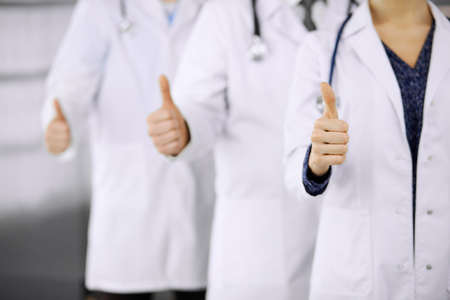 Doctors standing as a team with thumbs up in clinic and ready to help patients. Medical help, insurance and medicine concept.