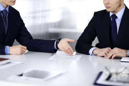 Business people discuss a contract, sitting at the desk in a modern office. Unknown businessman with a colleague, lawyers at negotiation. Teamwork and partnership concept