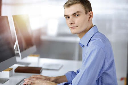 Young successful businessman works with computer, sitting at the desk in a sunny modern office. Headshot of male entrepreneur or it-specialist at workplace. Business concept