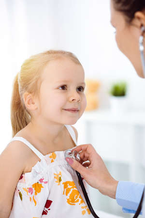 Doctor examining a child by stethoscope in sunny clinic. Happy smiling girl patient dressed in bright color dress is at usual medical inspection Banco de Imagens