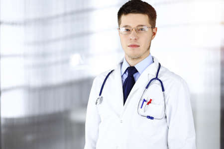 Doctor man with a stethoscope, is standing at his sunny hospital office. Perfect medical service in clinic. Happy future in medicine and healthcare